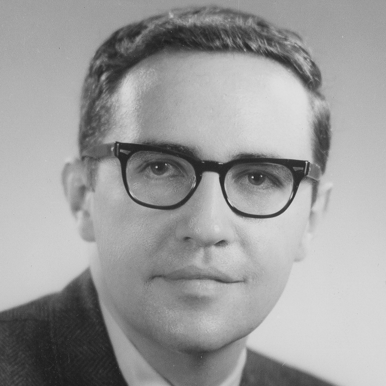 Black and white portrait of a young Ken Gros Louis. He is wearing a suit and black rimmed glasses.