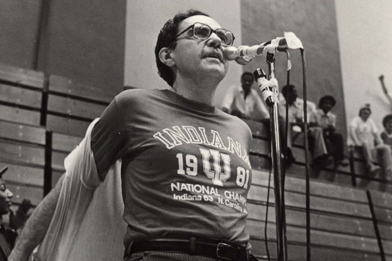 "A young Ken Gros Louis opens his button-down shirt to reveal a T-shirt underneath. The T-shirt says: ""Indiana 1981 National Champs, Indiana 63, N. Carolina 50."" He is standing in front of bleachers and speaking into a microphone."